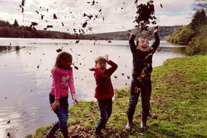 Children throwing leaves by a lake